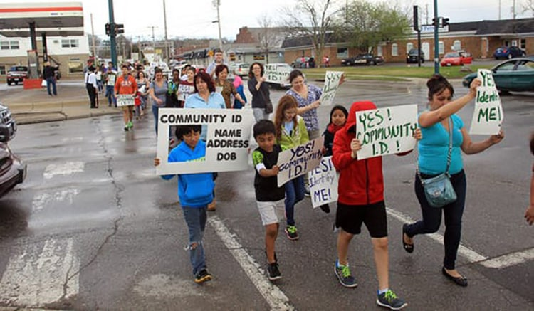 A group of people marching for community ID policies in their community