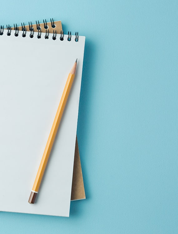 A notebook and pencil on a blue desk