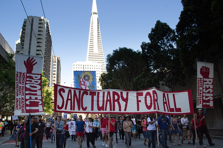 "A crowd marches and carries a banner that reads ""Sanctuary For All"""