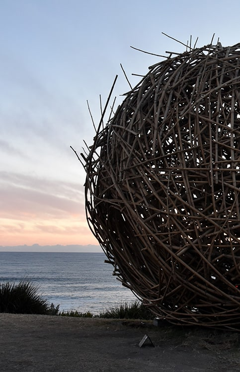 A large ball sculpture made of branches and twigs on a beach at sunset